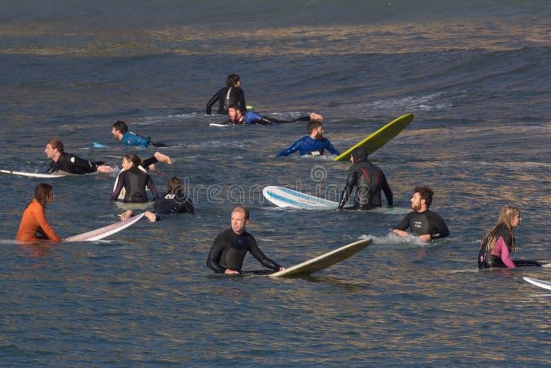 Группа в составе серферы ждет волну стоковая фотография