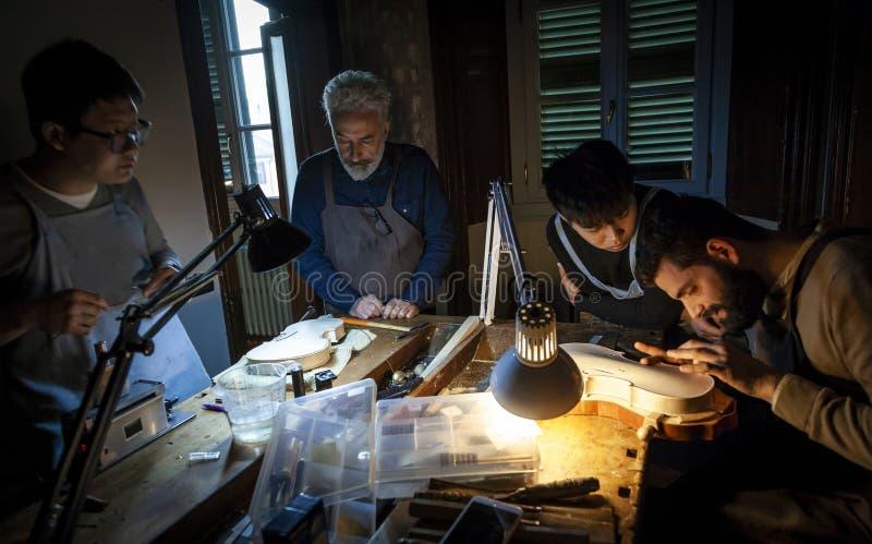 Группа в составе создатель скрипки мастеров работая на новой скрипке стоковые изображения rf
