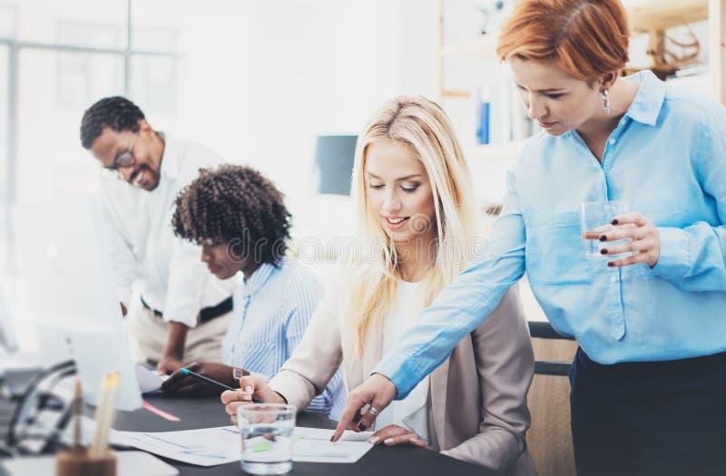 Группа в составе 4 сотрудника обсуждая бизнес-планы в офисе Молодые люди делая отличные идеи Горизонтальная, запачканная предпосы стоковое фото