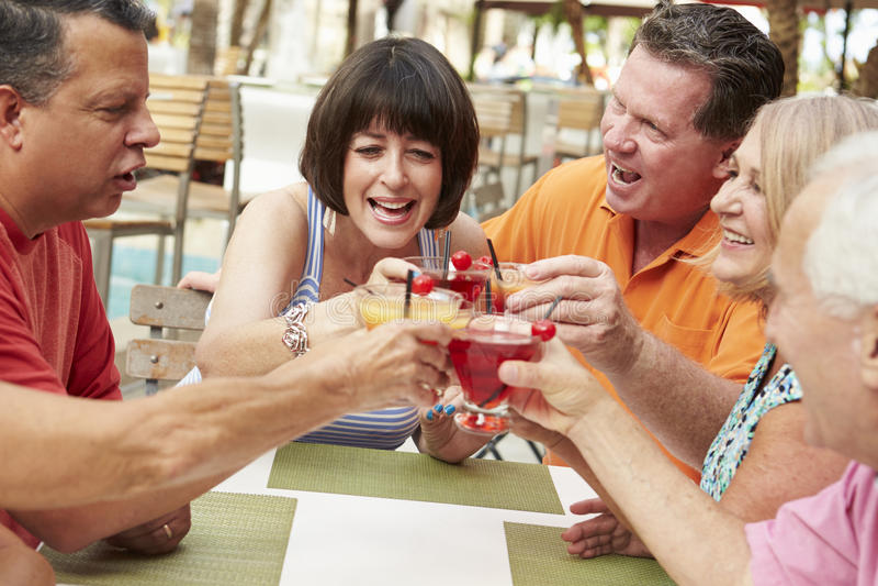 Группа в составе старшие друзья наслаждаясь коктеилями в баре совместно стоковые фото
