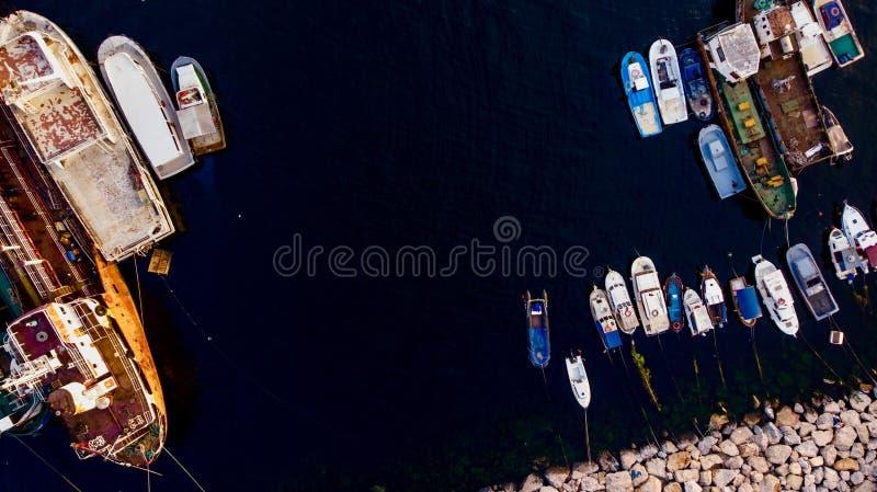 Группа в составе старые грузовие корабли, буксиры, удящ корабли и маленькие лодки в побережье около утесов стоковое изображение rf