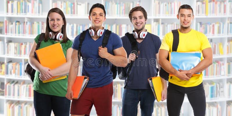 Группа в составе студенты изучает молодые людей библиотеки образования стоковое фото