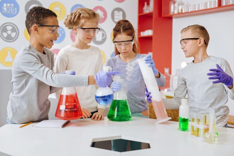 Группа в составе студенты наблюдающ реакциями в химическом стеклоизделии стоковое фото