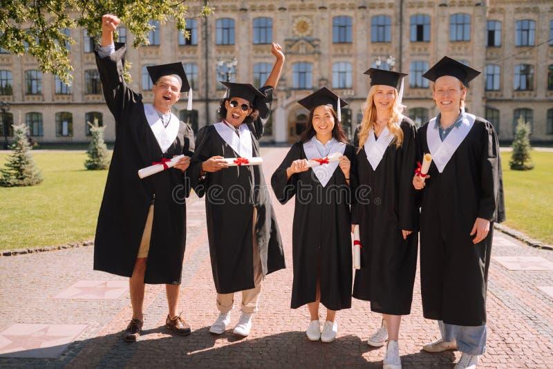 Группа в составе студенты стоя совместно после градации стоковое фото