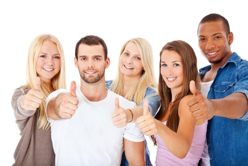 Группа в составе студенты показывая большие пальцы руки вверх стоковое изображение