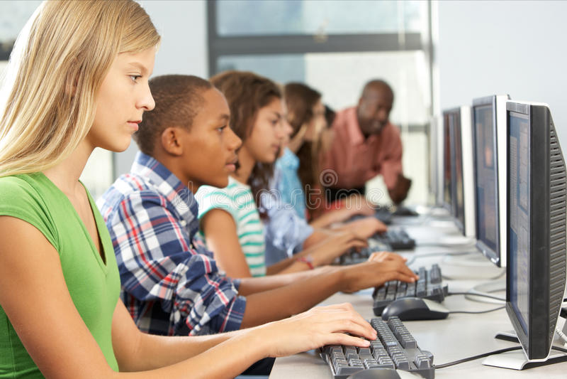 Группа в составе студенты работая на компьютерах в классе стоковое изображение rf
