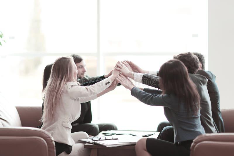 Группа в составе счастливые бизнесмены держа руки совместно пока сидящ вокруг стола стоковая фотография rf