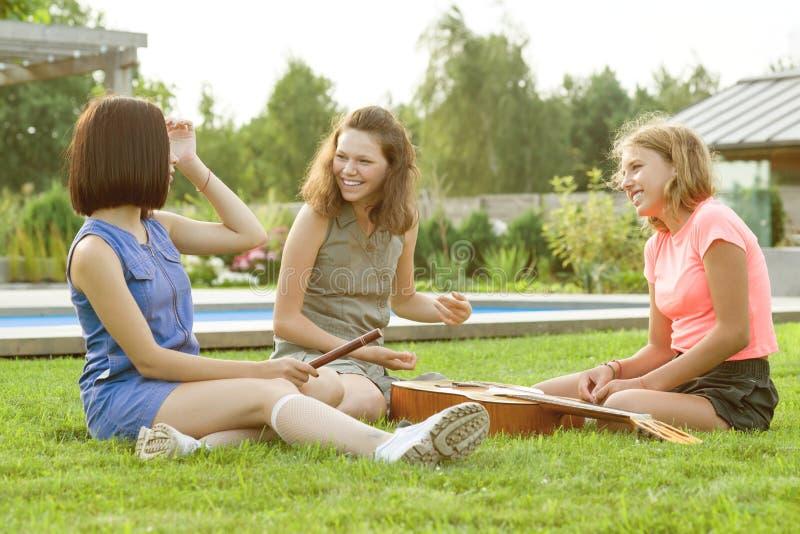 Группа в составе счастливые девочка-подростки имея потеху outdoors с гитарой Приведенный вверх с новой музыкой, сидите на зеленой стоковые изображения rf