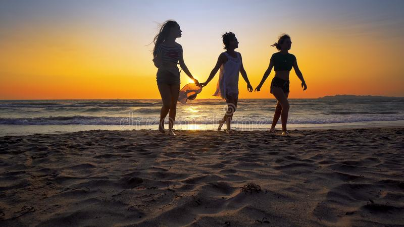 Группа в составе счастливые девушки бежать и играя на песке на пляже на заходе солнца стоковое изображение rf