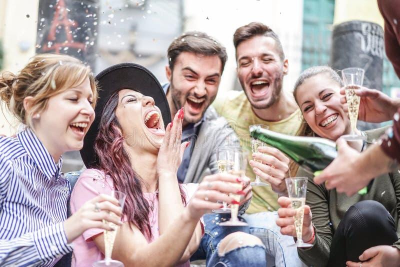 Группа в составе счастливые друзья делая confetti партии бросая и выпивая шампанское на открытом воздухе - молодые люди имея поте стоковые изображения