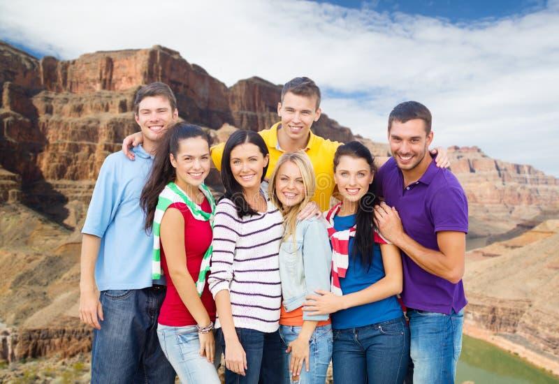 Группа в составе счастливые друзья над гранд-каньоном стоковая фотография