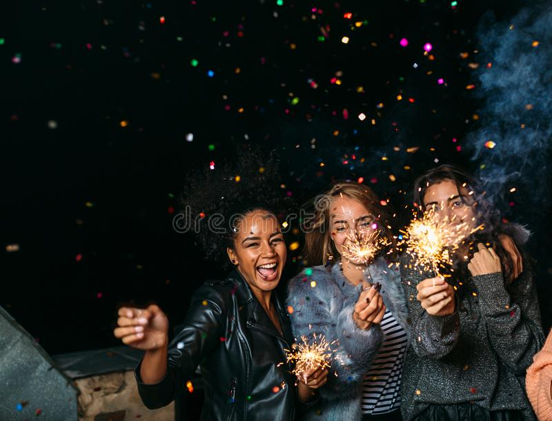 Группа в составе счастливые друзья празднуя канун ` s Нового Года стоковые изображения