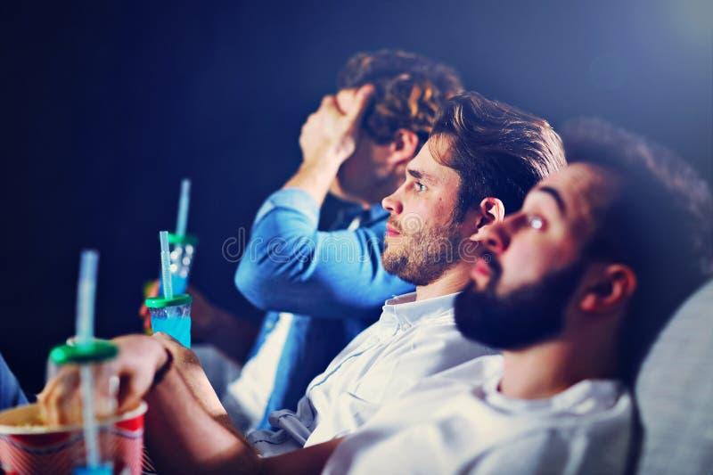 Группа в составе счастливые друзья сидя в фильме вахты кино и есть попкорн стоковое изображение
