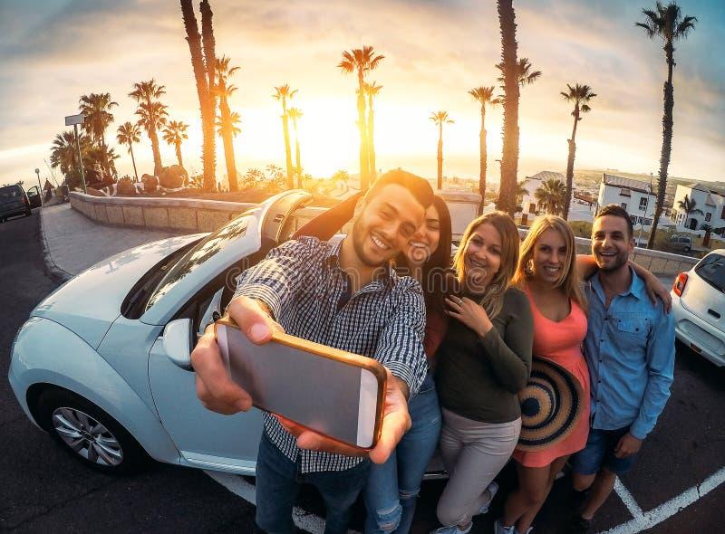Группа в составе счастливые друзья стоя перед обратимым автомобилем и принимая selfie с мобильным телефоном стоковое изображение rf
