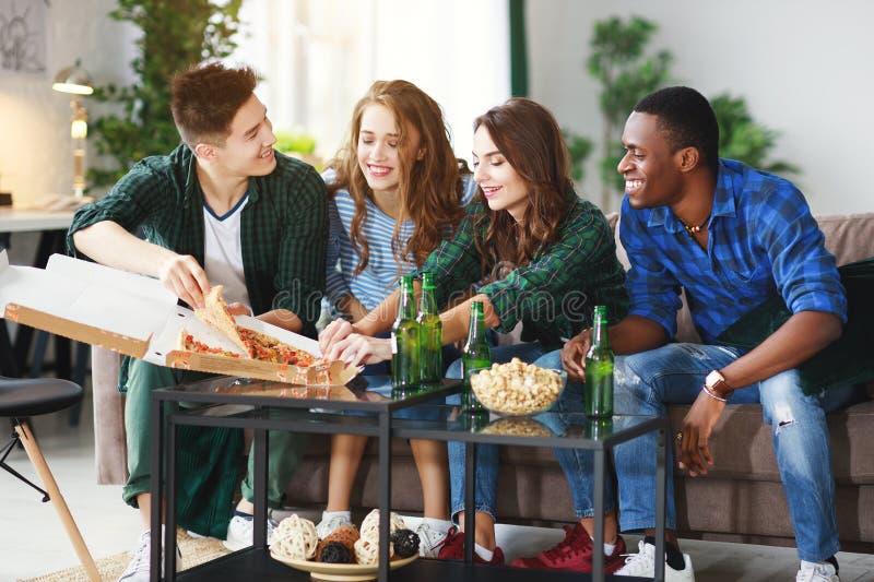 Группа в составе счастливые друзья с пивом и пиццей дома стоковое фото
