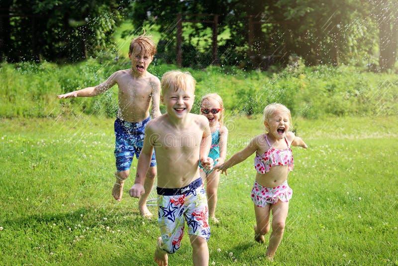 Группа в составе счастливые маленькие ребята усмехается по мере того как они бегут через снаружи спринклера на летний день стоковое изображение
