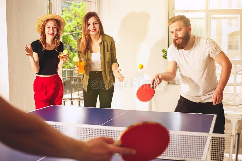 Группа в составе счастливые молодые друзья играя настольный теннис пингпонга стоковая фотография