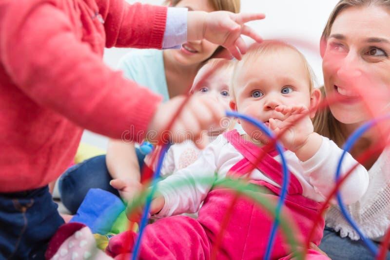 Группа в составе счастливые молодые матери наблюдая их милых и здоровых младенцев играет стоковые изображения rf