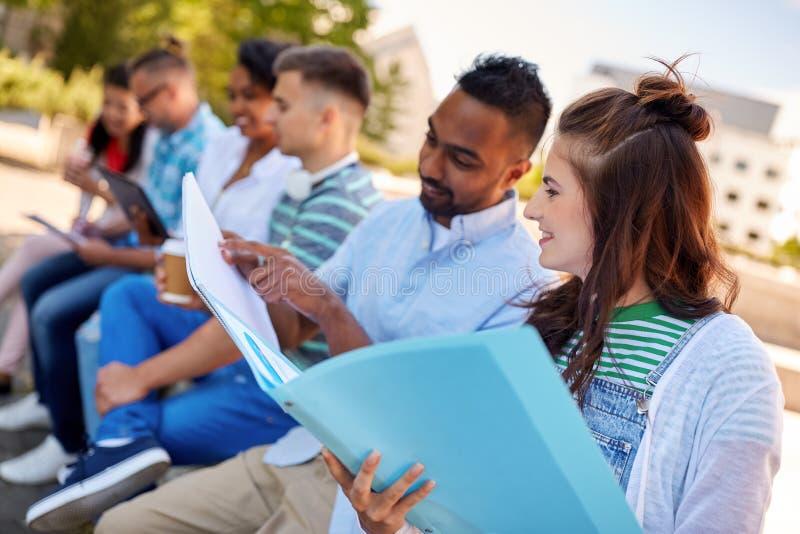 Группа в составе счастливые студенты с тетрадями outdoors стоковая фотография rf