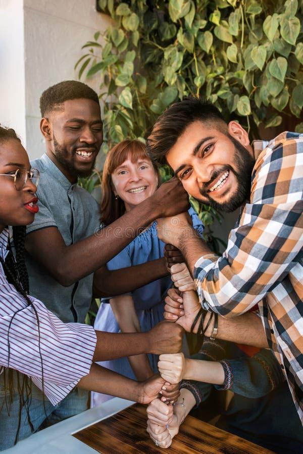 Группа в составе счастливые multiracial большие пальцы руки друзей вверх совместно стоковые фотографии rf