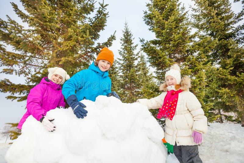 Группа в составе счастливое строение детей за стеной снега стоковое фото rf