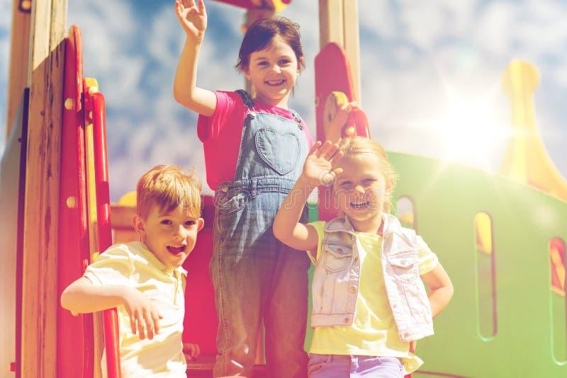 Группа в составе счастливые дети развевая руки на спортивной площадке стоковое фото