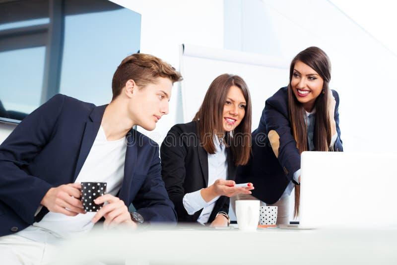 Группа в составе счастливые молодые бизнесмены в встрече на офисе стоковые изображения