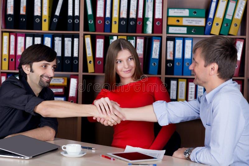Группа в составе счастливые молодые бизнесмены тряся руки стоковое фото