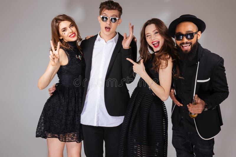Группа в составе счастливые молодые друзья стоя и усмехаясь стоковые фото