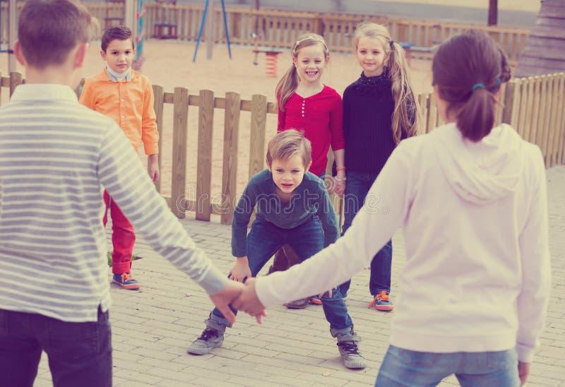 Группа в составе счастливые радостные дети играя красный вездеход стоковые фотографии rf