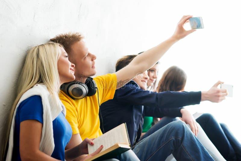 Группа в составе счастливые студенты находясь на проломе принимая selfie стоковое фото rf