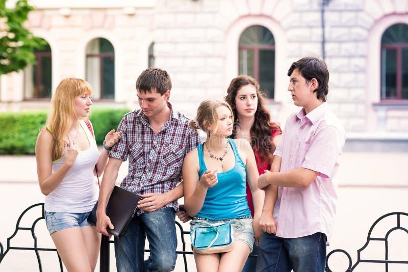Группа в составе счастливые усмехаясь подростковые студенты вне коллежа стоковые фото
