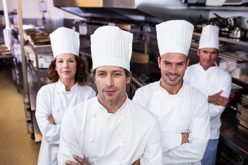 Группа в составе счастливые шеф-повара усмехаясь на камере стоковое фото
