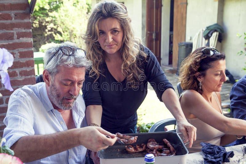 Группа в составе счастливые люди ест мясо outdoors стоковая фотография rf
