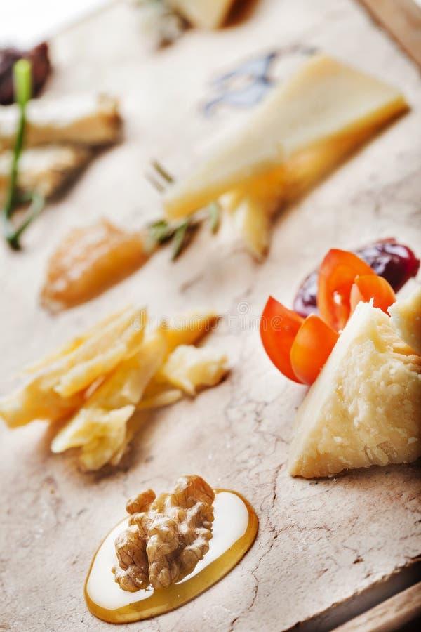 Cheeseboard с итальянскими сырами готовыми для degustation. Лакомка стоковое изображение