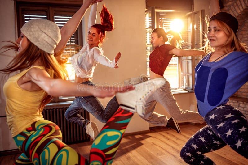 Группа в составе тазобедренные девушки хмеля скача во время музыки стоковые фотографии rf