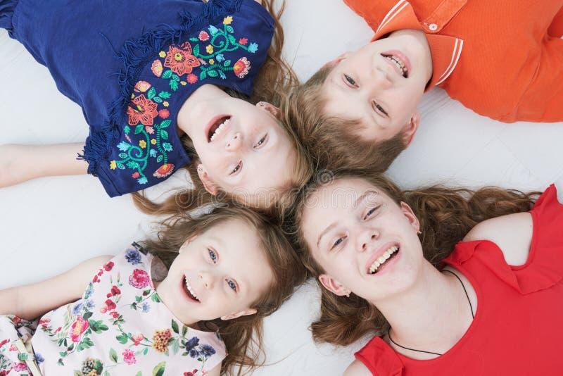 Группа в составе усмехаться 4 дет кладя на пол Верхний взгляд стоковое изображение