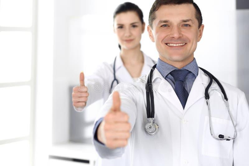 Группа в составе усмехаться докторов жизнерадостный на камере, больших пальцах руки вверх Идеальное медицинское обслуживание в кл стоковые фото