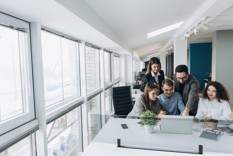 Группа в составе усмехаясь воодушевленные молодые бизнесмены работая совместно в офисе стоковое изображение rf