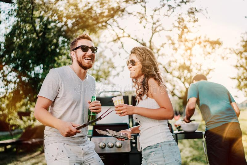 Группа в составе усмехаясь друзья в каникулах имея пив и варя на барбекю сада Образ жизни, концепция отдыха стоковая фотография