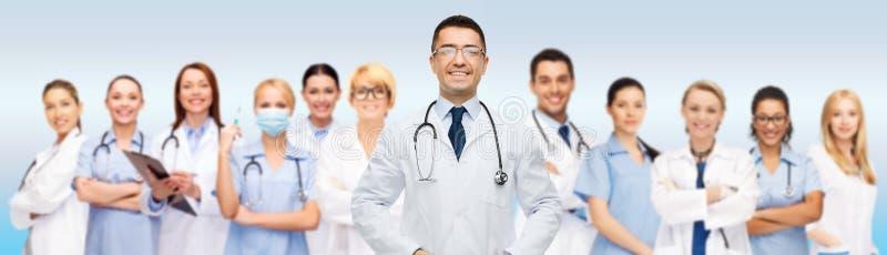 Группа в составе усмехаясь доктора с доской сзажимом для бумаги над серым цветом стоковые фото