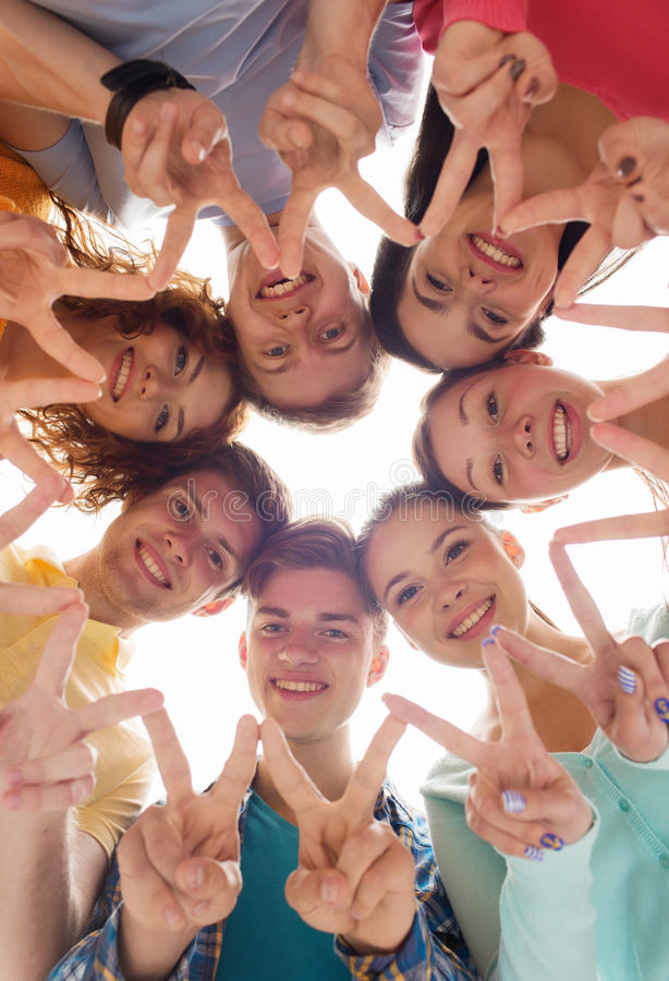 Группа в составе усмехаясь подростки показывая знак победы стоковое фото