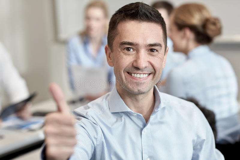 Группа в составе усмехаясь предприниматели встречая в офисе стоковая фотография rf