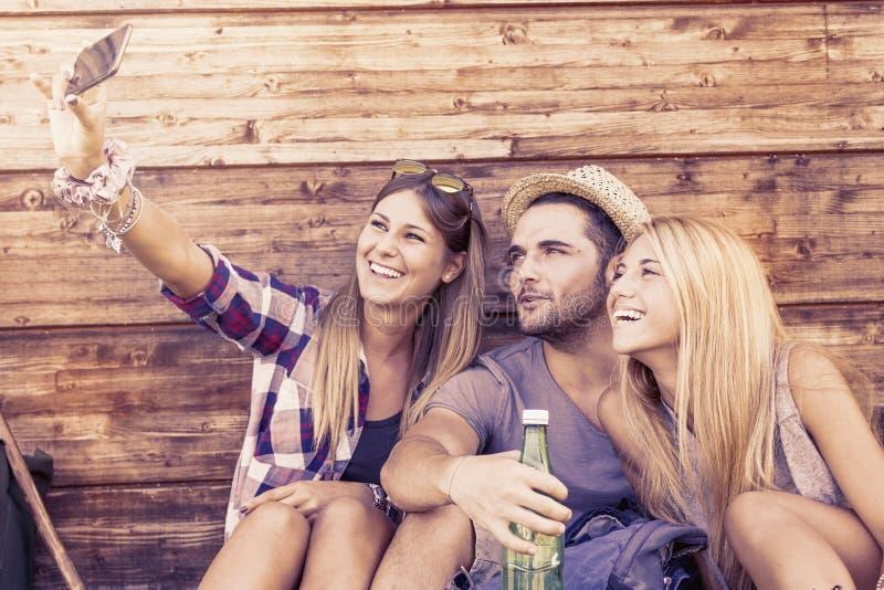 Группа в составе усмехаясь друзья принимая смешное selfie стоковые фотографии rf