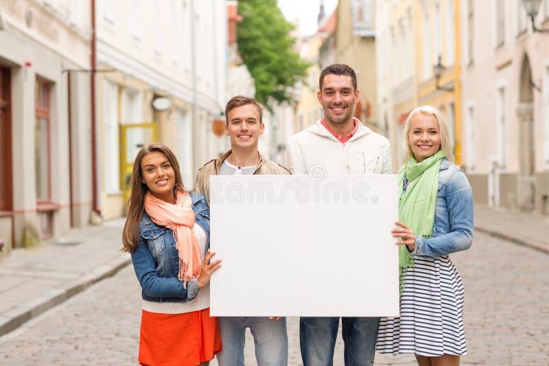 Группа в составе усмехаясь друзья с пустой белой доской стоковые фотографии rf