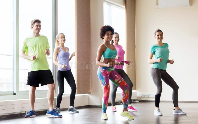 Группа в составе усмехаясь люди танцуя в спортзале или студии стоковое фото rf