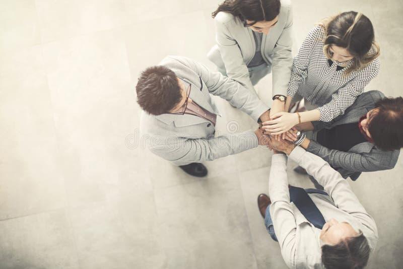 Группа в составе успешные бизнесмены руки к руке стоковое изображение
