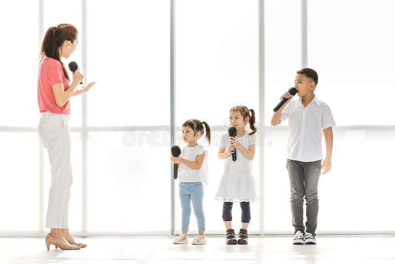 Группа в составе учителя уча дети, который нужно спеть стоковые изображения