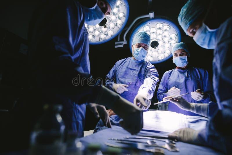Группа в составе хирурги в театре operating стоковое изображение