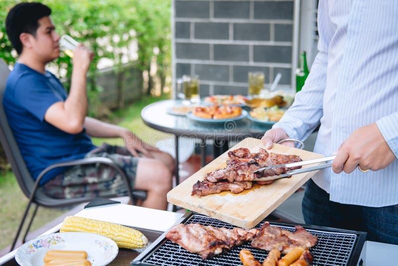 Группа в составе человек друзей 2 молодой наслаждаясь зажаренным мясом и поднять стекло пива для того чтобы отпраздновать выпиват стоковое изображение